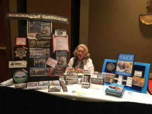 Author Kate Kuligowski posing at the NMDOG table at the NM Humane Conference